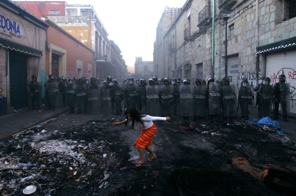 Una mujer pasa frente a un bloqueo de la policía en el centro de Oaxaca de Juárez, Oaxaca. Esto sucedió después de que manifestaciones ocurrieran para exigir la renuncia del gobernador del Estado, Ulises Ruiz.