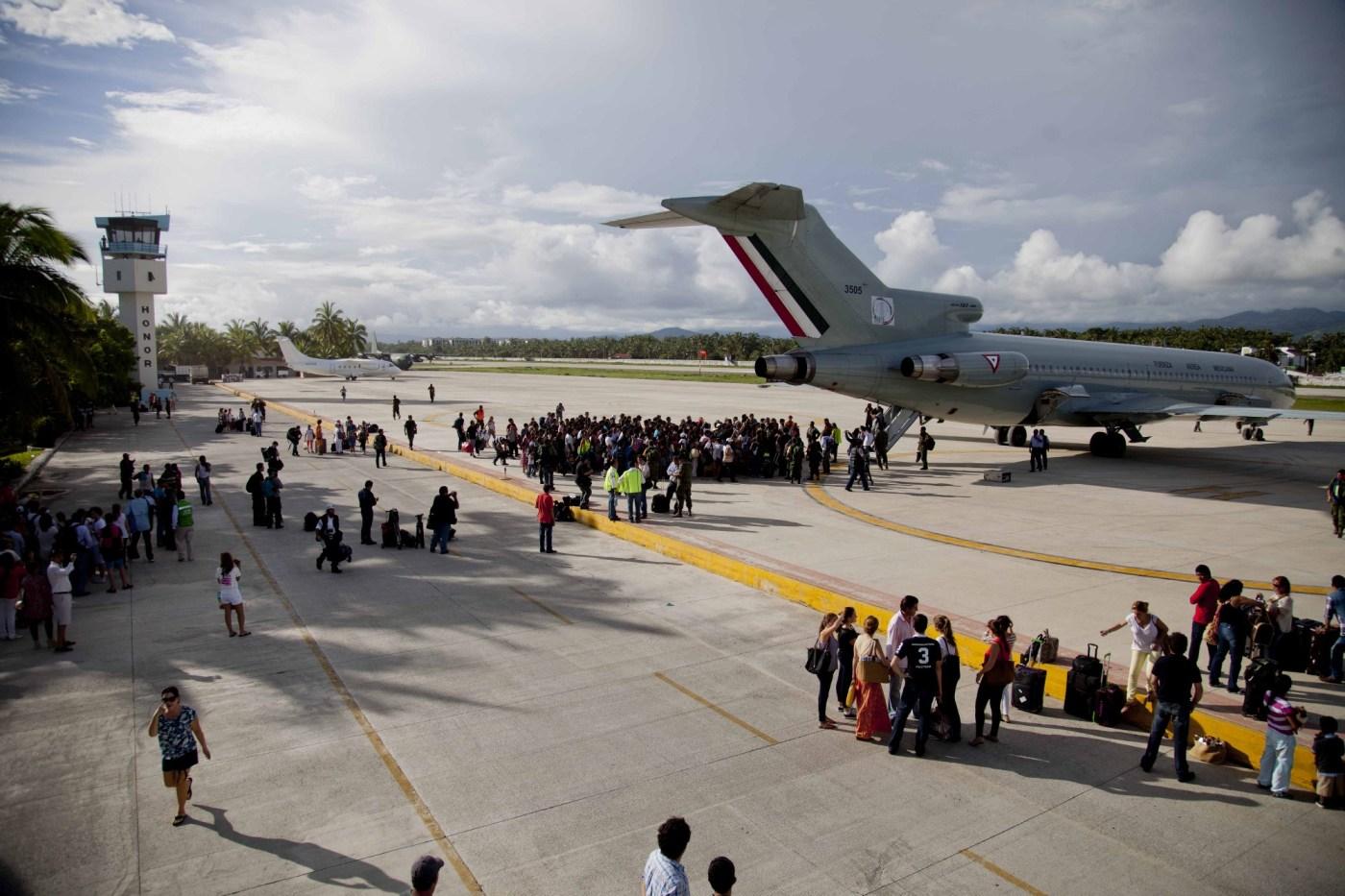 Cientos de turistas se reúnen afuera de un avión de la Fuerza Aérea Mexicana para ser evacuados en la base Pie de la Cuesta, cerca de Acapulco tras una tormenta tropical en el año 2013.