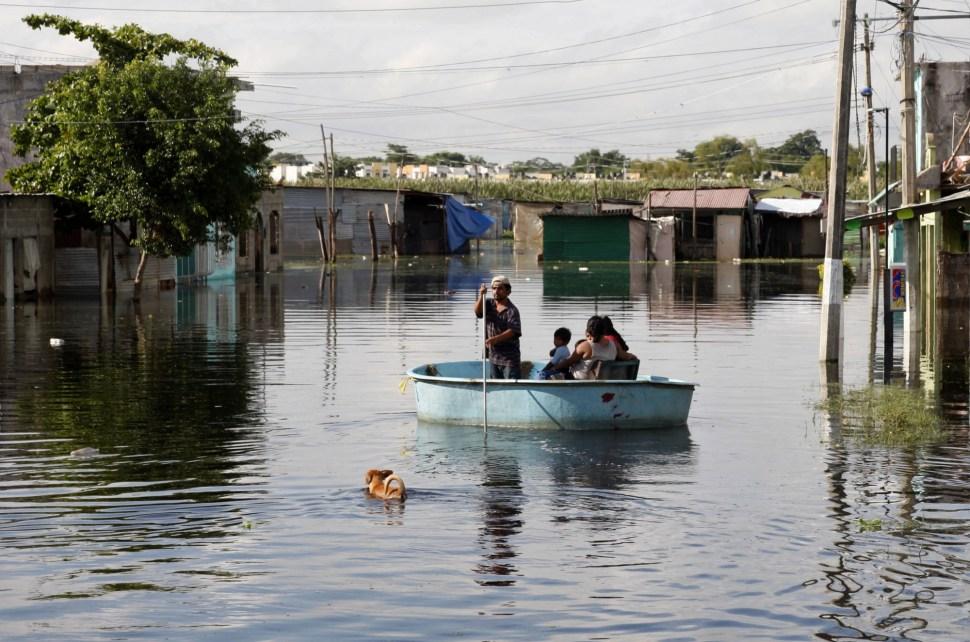 Un pequeño grupo de gente usa una balsa en una avenida inundada en Villahermosa, Tabasco.