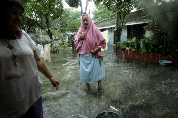 En el pueblo de Sabancuy, María Hernández, 72 años, camina con una toalla en la cabeza afuera de su casa inundada tras la llegada del huracán Dean.