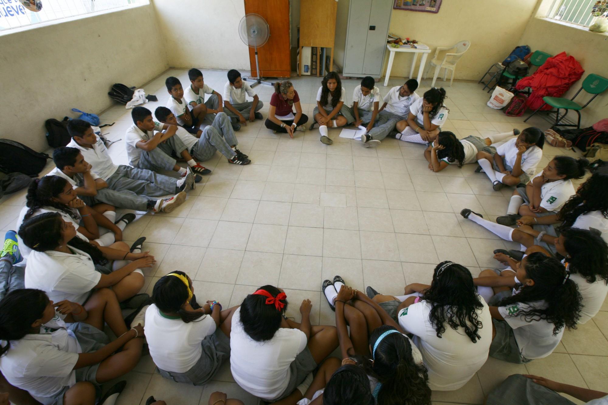 Estudiantes de una primaria en Acapulco se sientan en círculo para una clase.
