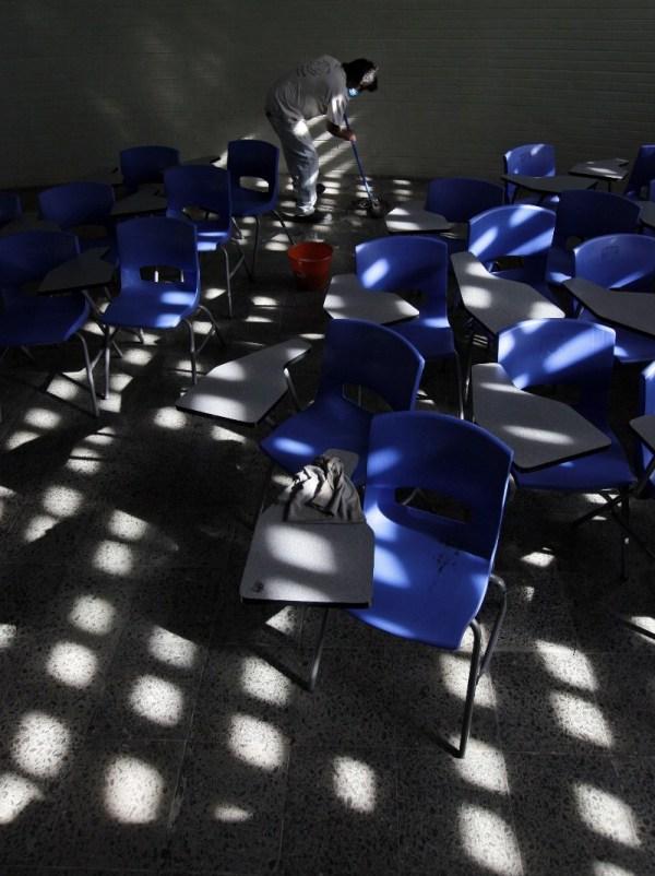 Un hombre usa un tapabocas para limpiar el salón en el año 2009 cuando hubo un fuerte brote de influenza, provocando el cierre por cuestiones sanitarias de escuelas.