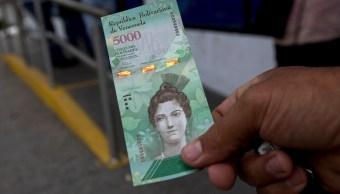Un hombre muestra un nuevo billete de 5,000 bolívares afuera de un banco en Caracas, Venezuela (AP)