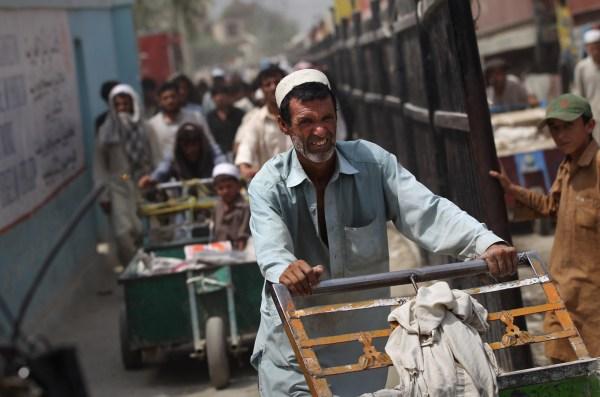 Afganos cruzando la frontera a Pakistán por el paso Torkham, importante por ser el lugar por el cual la base militar estadounidense en Afganistán importa más del 30% de las armas.