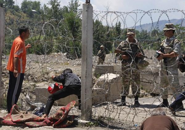 Uzbekos cruzan la frontera entre ambos países para abandonar Kirguistán mientras los observan los guardias fronterizos uzbekos.