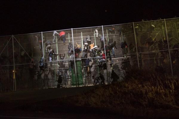 Personas procedentes de países subsaharianos intentan cruzar la gran valla que separa el enclave español de Melilla de Marruecos