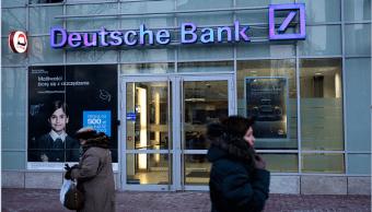 Varias personas caminan cerca de una sucursal del Deutsche Bank en Polonia.