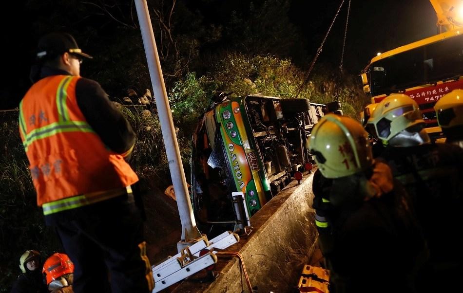 Un grupo de rescatistas se reúnen alrededor de un autobús volcado en Taipei, Taiwán donde viajaban 45 personas (Reuters)
