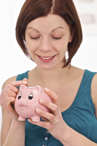 Imagen ilustrativa de una mujer ahorrando su dinero en una alcancía (Getty Images)