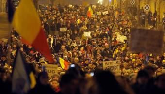 Cientos de miles de manifestantes marchan frente al edificio del gobierno durante una protesta en Bucarest, Rumania. (AP)