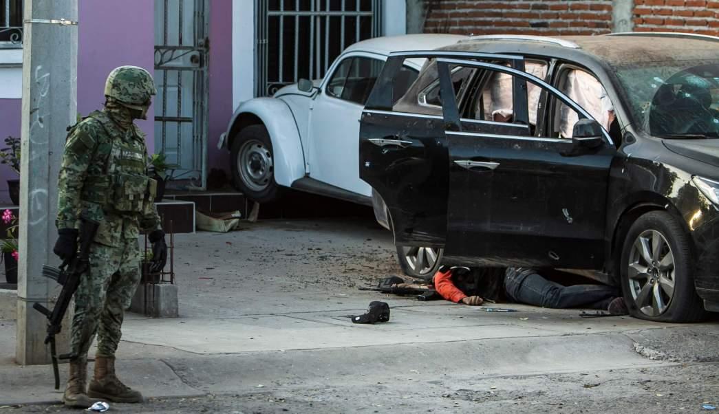 Un marino mira el cuerpo de un hombre al lado de un vehículo, tras un tiroteo en Culiacán, Sinaloa. (AP, archivo)