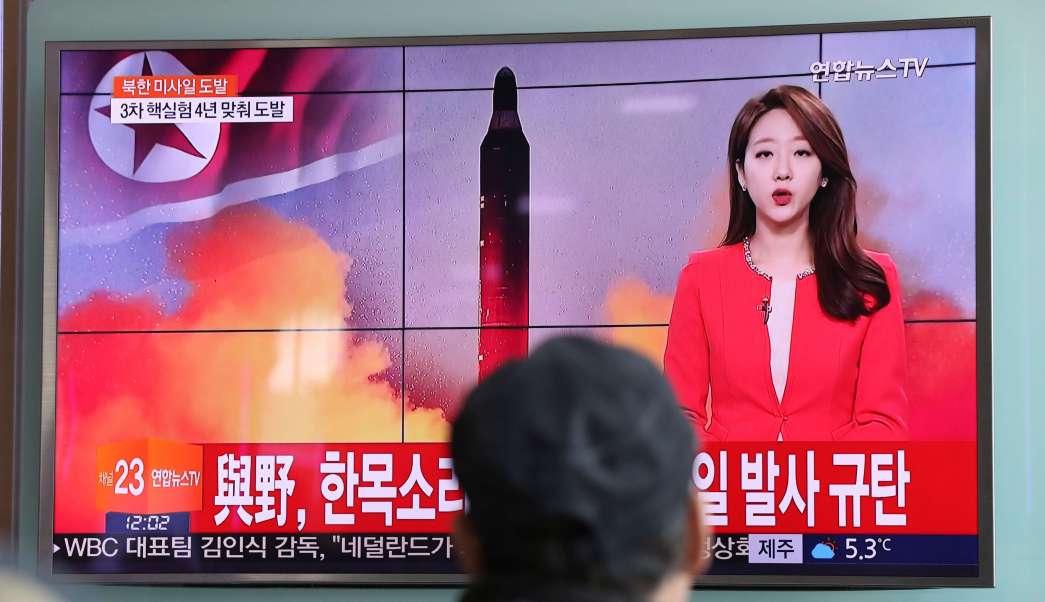Un hombre observa un noticiero en el que se informa del lanzamiento de misiles de Corea del Norte, con una imagen de archivo de un misil norcoreano. (AP)