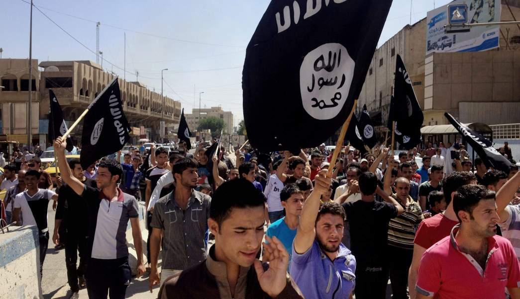 Simpatizantes del Estado Islámico de Irak portan banderas frente a la sede del gobierno provincial en Mosul. (AP)