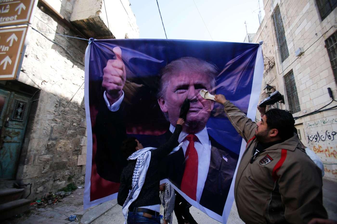 Durante las protestas en la ciudad de Hebrón, algunos palestinos pintaron consignas sobre un cartel del presidente estadounidense Donald Trump . (AP)