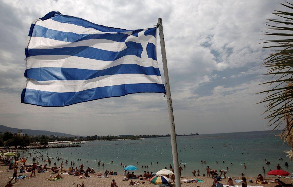 Vista de una bandera griega frente a una concurrida playa en un suburbio de Atenas, Grecia (AP)
