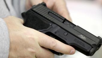 Un hombre sostiene una pistola mientras realiza compras en un establecimiento en Texas, EU (AP)