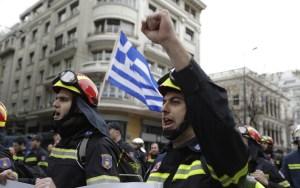 Bomberos cantan lemas frente a una bandera griega durante una protesta en el centro de Atenas, para exigir mejores condiciones de contratación (AP)