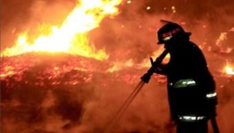 Bombero labora para sofocar un incendio que se registró en la carretera México-Cuernavaca; el incidente es controlado (NTX)