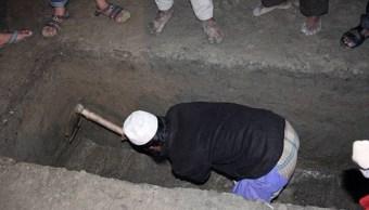 Un hombre cava una tumba durante una ceremonia de entierro en India (Getty Images/archivo)