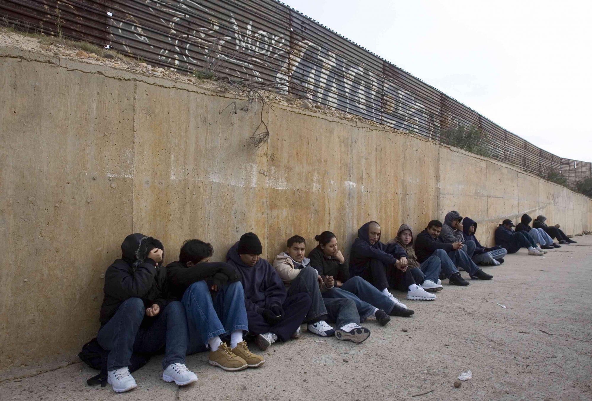 En esta foto de 2008, migrantes esperan junto a la barda fronteriza de Tijuana para cruzar por la noche.