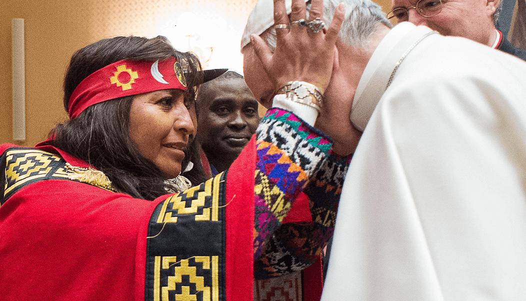Mujer indígena toma con sus manos el rostro del papa Francisco, durante un encuentro de éste con comunidades indígenas. (AP)