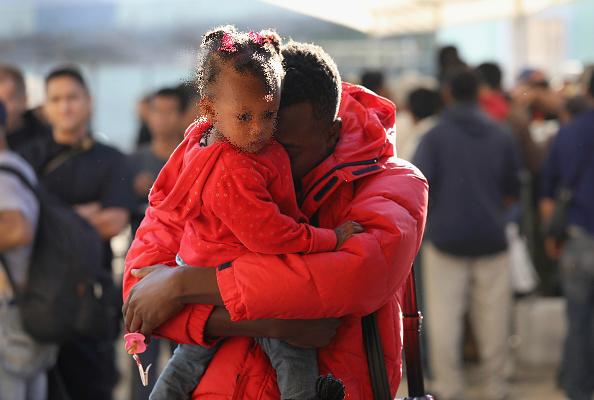 Haitianos en espera de recibir ayuda en un centro para migrantes en Tijuana; autoridades educativas de Baja California planean dar educación a los niños de ese país