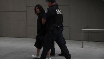 Un oficial de la patrulla fronteriza detiene un joven migrante en San Ysidro, California.