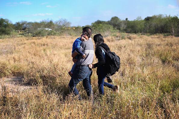 Un padre carga a su hijo durmiente para cruzar ilegalmente la frontera de los Estados Unidos con México cerca de la ciudad de Rio Grande, Texas. (Getty Images)