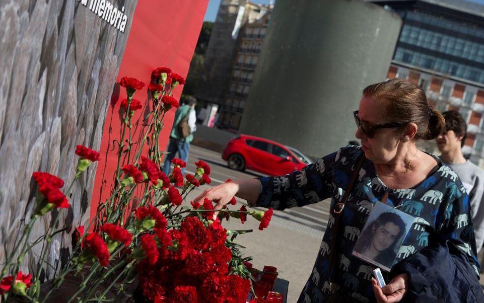Un pariente de una víctima de los atentados del tren de Madrid coloca una flor afuera de la estación de Atocha en el 13 aniversario de los atentados (Reuters)