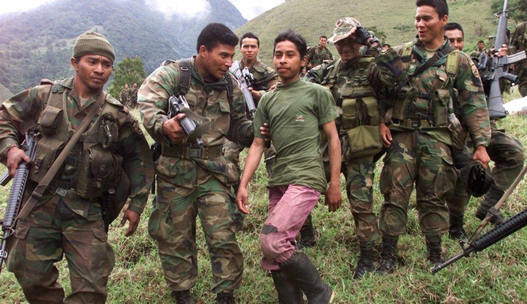 Soldados escoltan a un adolescente rebelde, de 13 años de edad, de las Fuerzas Armadas Revolucionarias de Colombia (FARC) que fue capturado en las montañas del estado de Santander, en el noroeste de Colombia. (AP/archivo)
