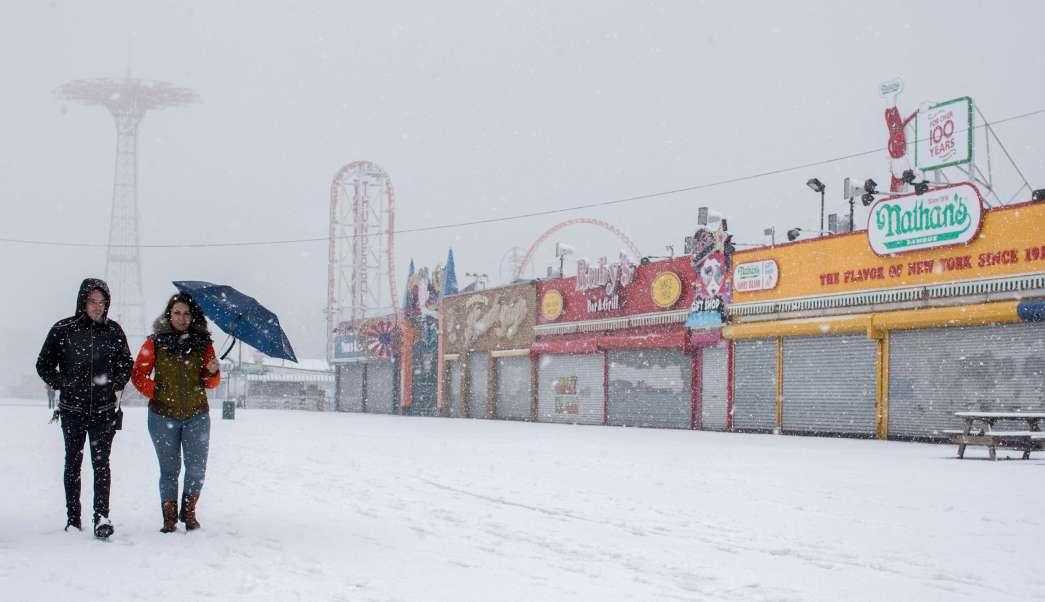 Una pareja camina en Coney Island, en Nueva York, durante una tormenta de nieve. (AP)