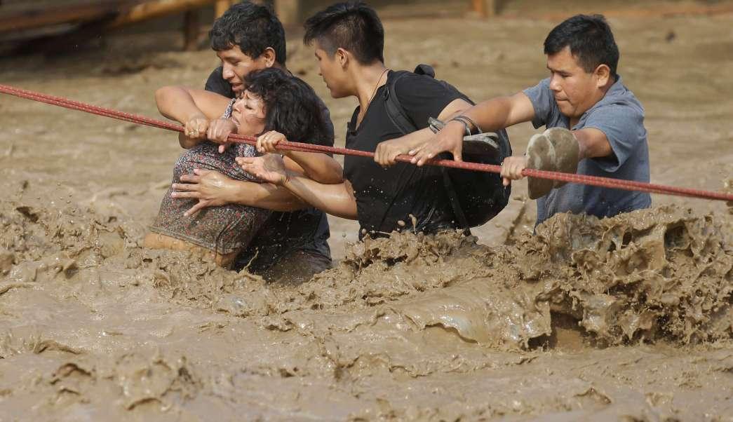 Un grupo de personas quedan atrapados en fuertes corrientes de agua tras las inundaciones en Lima, Perú. (AP)