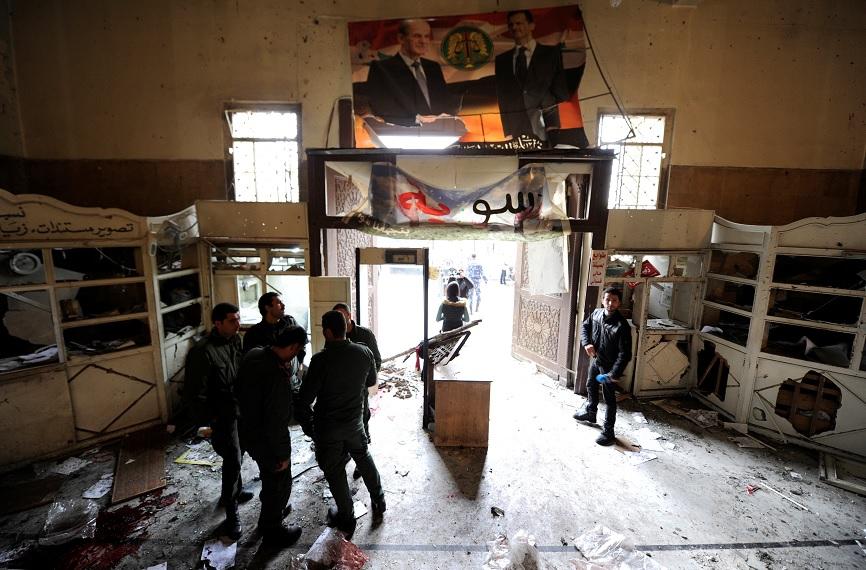 Personal de seguridad permanece cerca de una entrada dañada después de una explosión suicida en el palacio de justicia en Damasco, Siria, (Reuters)