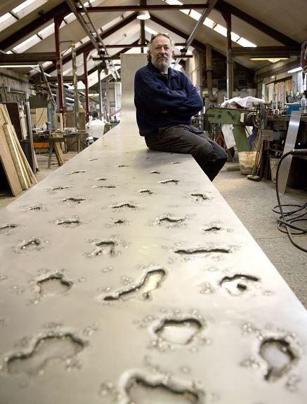 El artista belga posa sobre su escultura en su estudio de Florenville, Bélgica. (AP)