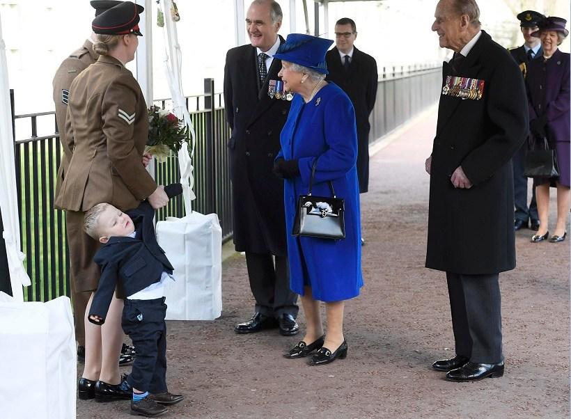 Michelle Lun, izquierda, aferra la mano de su hijo Alfie, de dos años, frente a Isabel II; el menor hace un berrinche frente a la reina (AP)