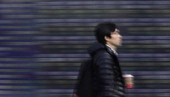 Un peatón camina frente a un tablero electrónico de la Bolsa de Tokio. (Getty Images)