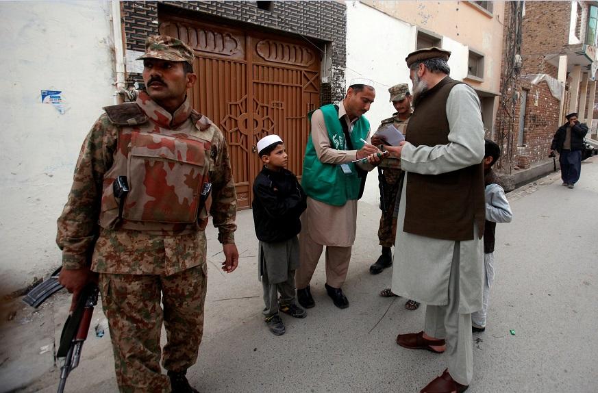 Militar a compaña a encuestador que realiza censo de población en Pakistán (Reuters)