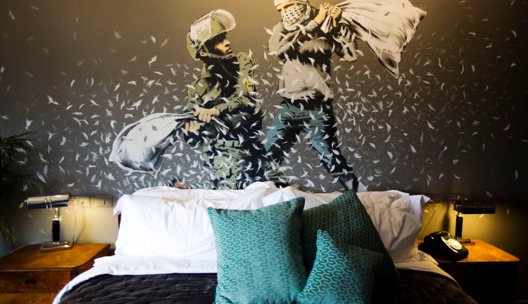 En el mural de Banksy que preside la habitación número tres, un Policía de Frontera y un palestino mantienen una lucha de almohadas. (AP)