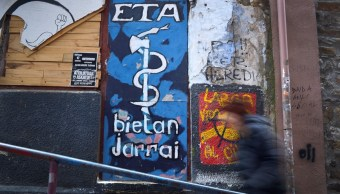 Una mujer pasa por un mural que representa el emblema de la serpiente y el hacha de los separatistas vascos ETA, en la localidad portuaria vasca de Bermeo (Reuters)
