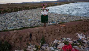 La activista medioambiental Maruja Inquilla posa para una fotografía junto a una planta municipal de tratamiento de residuos con agua que fluye al lago Titicaca. (AP)