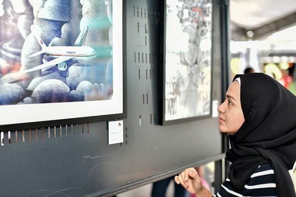 Una de las familiares de las víctimas mira una fotografía del vuelo 370 de Malaysia Airlines desaparecido (Getty Images)