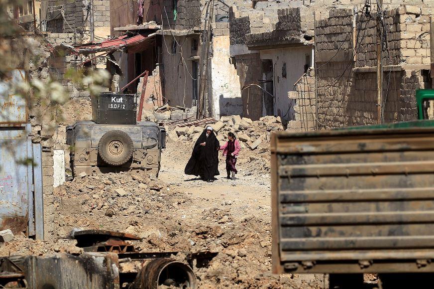 Iraquíes que decidieron quedarse en casa recogen paquetes de ayuda humanitaria mientras los combates entre las fuerzas de seguridad iraquíes y los combatientes del Estado islámico continúan en el oeste de Mosul. (Reuters)
