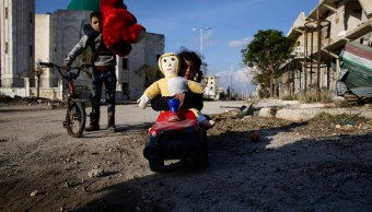 Niños sirios, que fueron desplazados tras un ataque, juegan mientras regresan a su casa en el distrito de Hanano, en Alepo. (Archivo/AP)