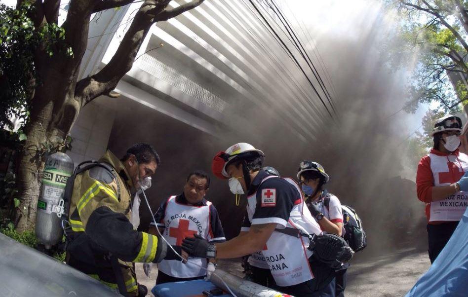 Paramédicos de la Cruz Roja atienden a un bombero intoxicado por el incendio registrado en el cruce de las calles Masaryk y Schiller. (@CruzRoja_MX )