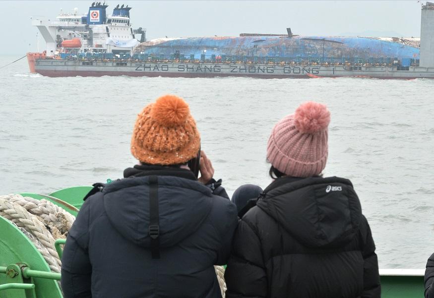 Familiares de las víctimas del naufragio de un ferry en Corea del Sur observan los trabajos de reflotamiento (Reuters, archivo)