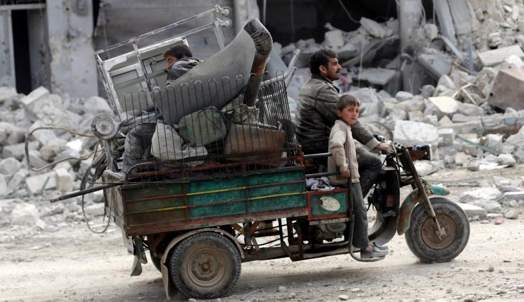 Una familia conduce un vehículo a través de un vecindario dañado en la ciudad siria del norte de al-Bab (Reuters)