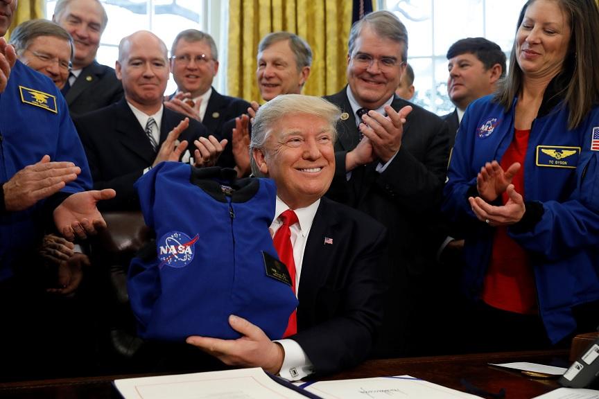 El presidente Donald Trump recibe una camisa de la NASA durante la ceremonia de firma de la S442, la ley de autorización de transición de fondos a la Agencia Espacial de EU (Reuters)