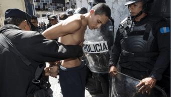 Un policía de Guatemala catea a un miembro de la pandilla Barrio 18 que participó en el motín. (AP)