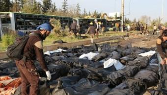 Miembros del equipo de defensa civil trasladan los cuerpos de las personas que murieron por un ataque con coches bomba contra un convoy de refugiados sirios (Getty Images)