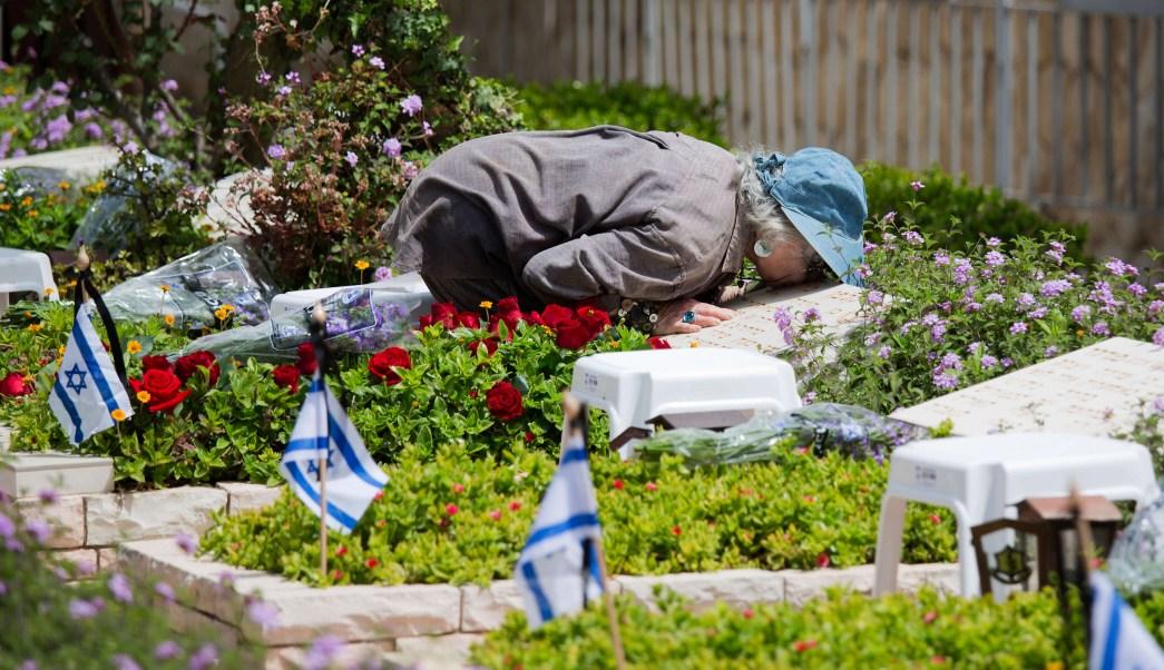 Una mujer besa la tumba de un soldado caído en una jornada en Israel. (AP)
